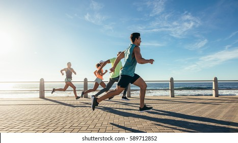 Portrait of young runners sprinting on the ocean front path. Group running along a seaside road.
