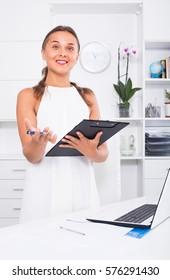 portrait of young russian woman in formal wear having clipboard in hands in office