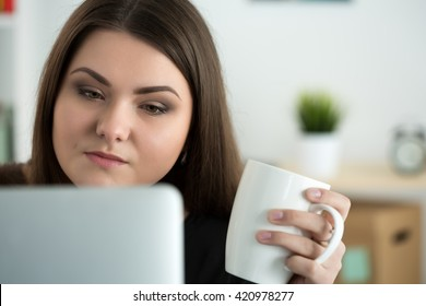Portrait of young sad or attentive woman looking at laptop monitor and holding white cap of tea. Online education, coffee break or dieting concept