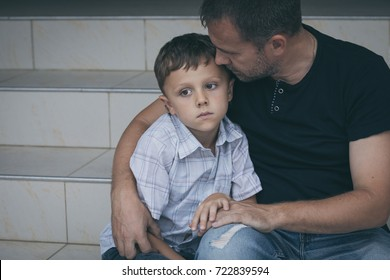 Portrait of young sad little boy and father sitting outdoors at the day time. Concept of sorrow.