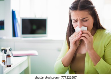 Portrait of the young sad sick woman who sitting in the office and wiping a nose with a napkin