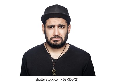 Portrait of young sad unhappy man with black t-shirt and cap looking at camera. studio shot, isolated on white background.