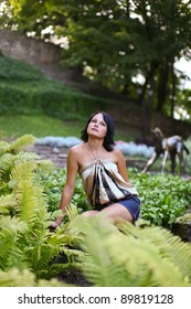 Portrait of young sadness woman which is sitting near to bush of fern in central park against sculpture of horse at Bastion hill in Riga, Latvia