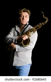 Portrait of a young saxophonist on a black background.