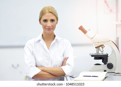 Portrait of a young scientist using a microscope in a lab