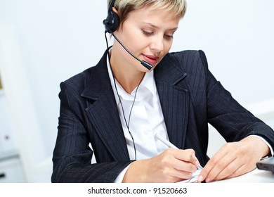 Portrait of young secretary with headset making notes
