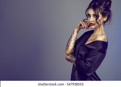 Portrait of young seductive tattooed dark-haired model with provocative make-up and updo hair wearing a black silk peignoir falling from her shoulder. Her hand at her face. Studio shot. Copy-space