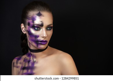 A portrait of a young, self-confident, daring and seductive girl. She is posing in a dark background demonstrating her character, image, makeup and the colorful highlights of the light on her face.