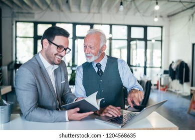 Portrait of young and senior business men working together.