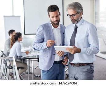 A portrait of a young and senior smiling business people holding a tablet during a meeting and presentation in the office. Business concept