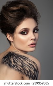 Portrait of young sensual brunette woman with black wing body art on her back