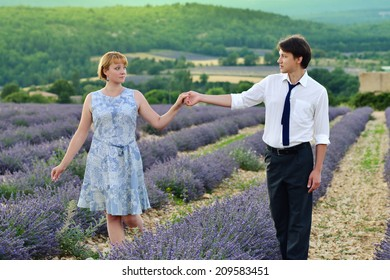 Portrait of young sensual loving couple in a lavender field at sunset. Provence, France