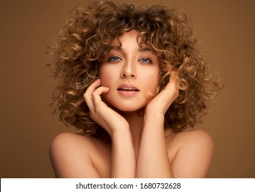 Portrait of young sensual woman with curly hair isolated on brown background