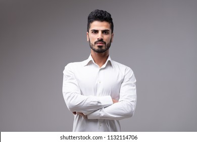 Portrait of young serious bearded man wearing white shirt standing with arms crossed