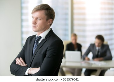 Portrait of young serious businessman calculating risks in investment, dreaming of high possible gains, thinking how to make morally correct decision, exploring new horizon. Boss and his team concept