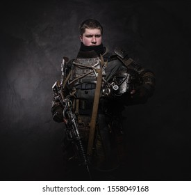 Portrait of young serious man in doomsday warrior's costume at dark photo studio.