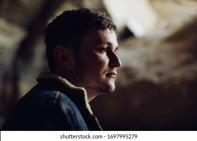 Portrait of a young serious man in the mountains in a cave