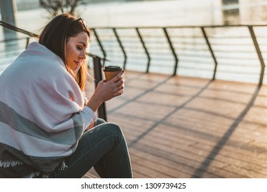 Portrait of young serious woman outdoors. Sad woman standing by the water during sunset. Beautiful woman very sad from unrequited love, rethink, think over, broken heart