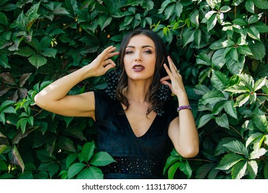 Portrait of young sexy brunette in black dress holding black grapes like an earrings.