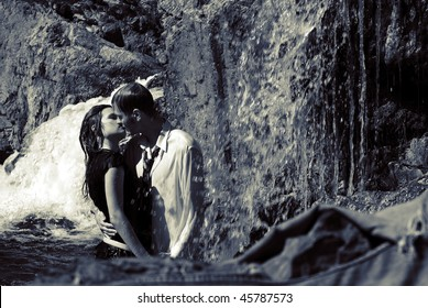 Portrait of a young sexy couple drinking a tea and making love on waterfall