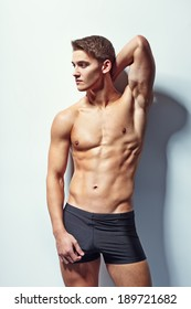Portrait of a young sexy muscular male model in underwear against white wall in sensual pose his hand behind his head