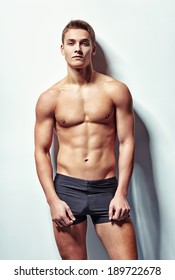 Portrait of a young sexy muscular man in underwear against white wall