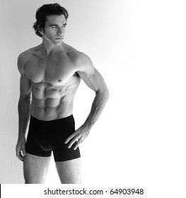 Portrait of a young sexy shirtless man in underwear against neutral background with lots of copy space