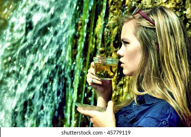 Portrait of a young sexy woman drinking a tea on waterfall