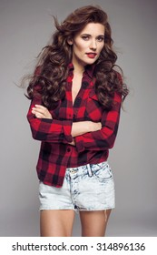 Portrait of young sexy woman in jeans shorts, red checked shirt, red lips. Fashion studio shot.