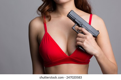 Portrait of young sexy woman in red bra holding a gun