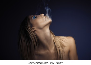 Portrait of young sexy woman while smoking cigarette against blue background