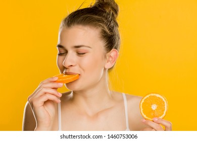 Portrait of young shirtles beautiful woman eating a orange on yellow background