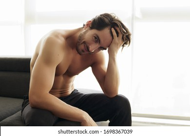 Portrait of Young Shirtless White Man With Beautiful Hair is smiling and looking at the camera. Athletic and Muscular Caucasian Male With fingers Through His Hair Looking Confident