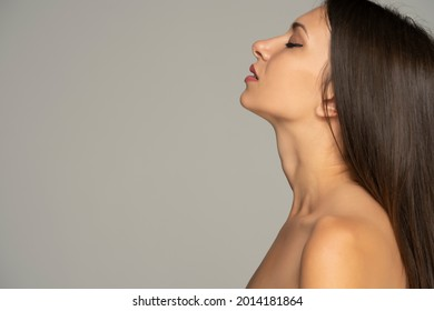 a portrait of a young shirtless woman with her head raised against a gray background