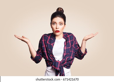 Portrait of young shocked brunette woman with casual style looking desperate or panic, keeping mouth open and making helpless gesture with her hands, doesn't know what to do.