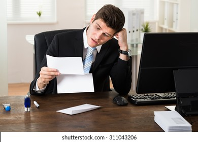Portrait Of Young Shocked Businessman Looking At Document In Office
