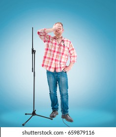 Portrait of a young showman or stand-up comic with the microphone. Blue background. Show concept.