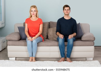 Portrait Of Young Shy Couple Sitting On Sofa At Home