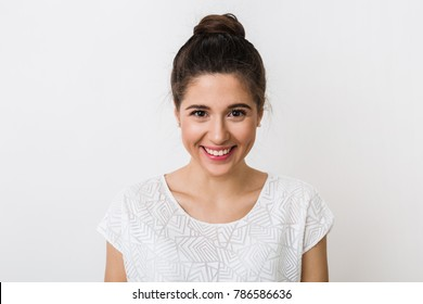 portrait of young sincere smiling woman in white blouse, positive face expression, looking into camera, natural, isolated on studio background