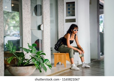 Portrait of a young Singaporean Chinese Asian millennial teenager sitting on a bench in the city. She is wearing a pair of sunglasses and street wear and enjoying a drink as she waits for a friend.