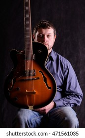 portrait from a young singer with his guitar on black background