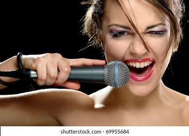 portrait of a young singer with a microphone on a black background