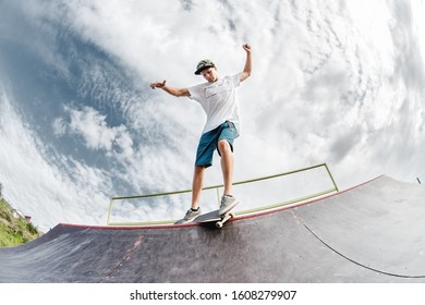 Portrait of a young skateboarder doing a trick on his skateboard on a halfpipe ramp in a skate park in the summer on a sunny day. The concept of youth culture of leisure and sports
