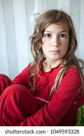 portrait of young sleepy girl eleven years old in red pyjamas sitting on the bed