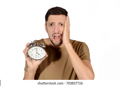 Portrait of young sleepy man with alarm clock. Isolated white background.