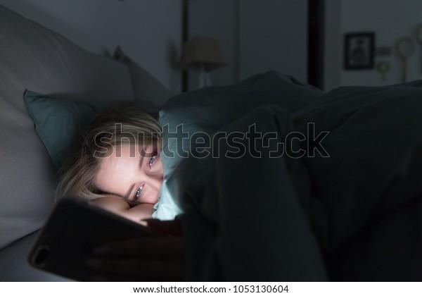 Portrait d'une jeune femme fatiguée endormie, allongée sous la couverture, à l'aide d'un smartphone tard dans la nuit, incapable de dormir/ Insomnie, nomophobie, concept de trouble du sommeil/ Dépendance à un téléphone portable