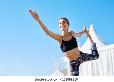 Portrait of a young slim athletic sports woman makes yoga exercises and stretching on the pier at sunny summer morning. Athletic lady doing Lord of Dance pose against blue sky.Natarajasana Yoga Pose