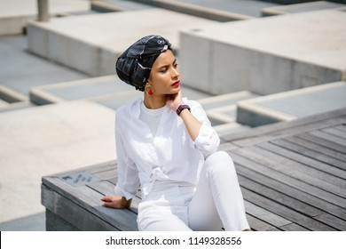 Portrait of a young, slim Muslim woman in a turban head scarf (hijab) and a pristine white outfit posing in the sun in the city. She is tall, elegant and beautiful.