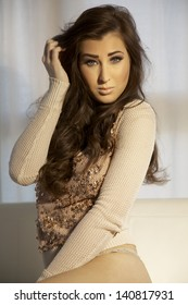 Portrait young slim sexy and attractive brunette woman in brown sweater on the sofa