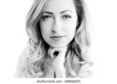 Portrait of young slim woman smiling in studio in black and white